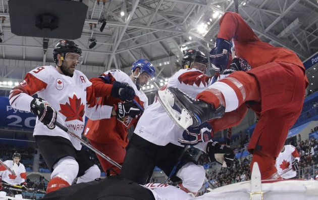 Canada's Mat Robinson pushes Czech Republic's Michal Repik in the men's bronze medal hockey match between...