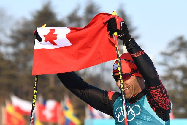 Tonga's Pita Taufatofua holds up his national flag after crossing the finish line during the men's 15km...
