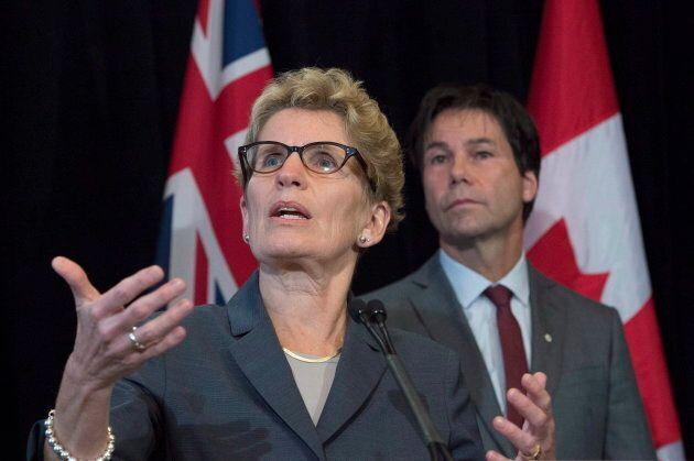 Ontario Premier Kathleen Wynne speaks as former health minister Eric Hoskins looks on in Toronto on Oct....