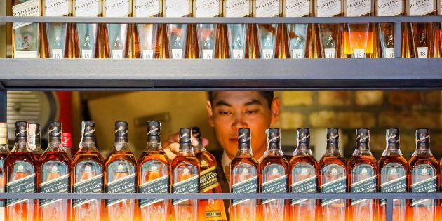 A bartender takes a bottle of Johnnie Walker whisky at Barmaglot bar in Almaty, Kazakhstan June 22,