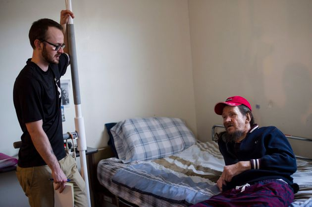 Case worker Jake McPhee speaks to Bruce Hughes in his room at the Art Manuel House in Toronto on Tuesday,...