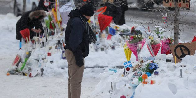 A man looks at the memorial near the site of a fatal shooting at the Quebec Islamic Cultural Centre in...
