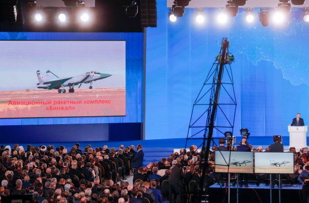 The video screen shows the Kinzhal air missile system as President Vladimir Putin (R back standing) delivers...