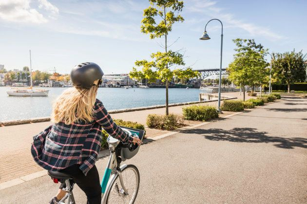 A woman rides a bicycle along the Vancouver