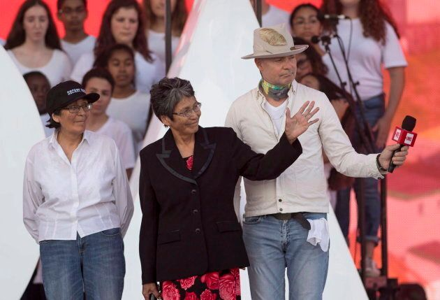 Daisy Wenjack, left, Pearl Wenjack and Tragically Hip frontman Gord Downie acknowledge the crowd at We...
