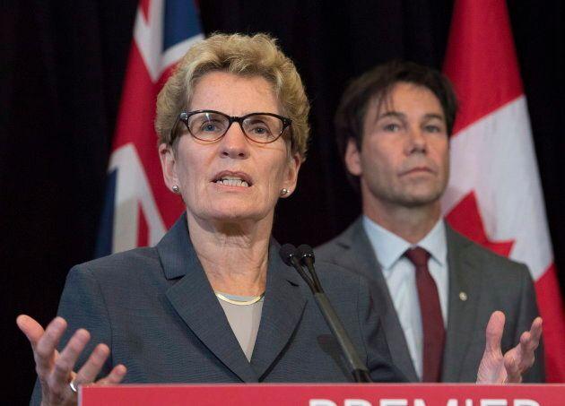Ontario Premier Kathleen Wynne, left, speaks as now-former Health Minister Eric Hoskins looks on.