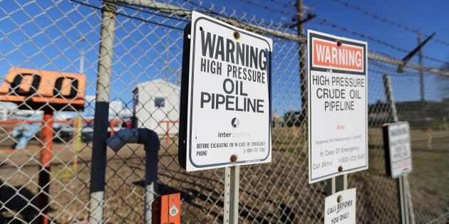 Signs warning of the presence of oil pipelines are seen on a fence at