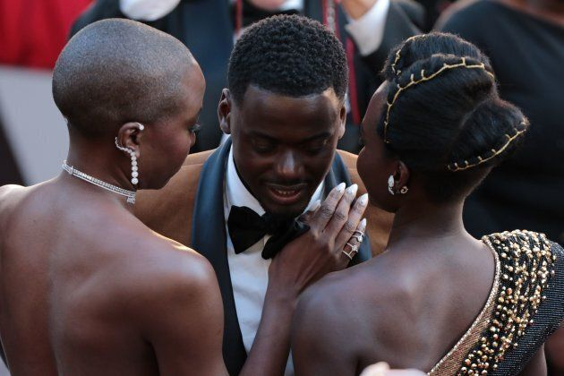 Danai Gurira, Daniel Kaluuya and Lupita Nyong'o share a moment on the Oscars red carpet. Caption