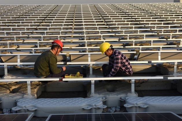 Workers install solar panels at a floating solar plant in Huainan, Anhui province,