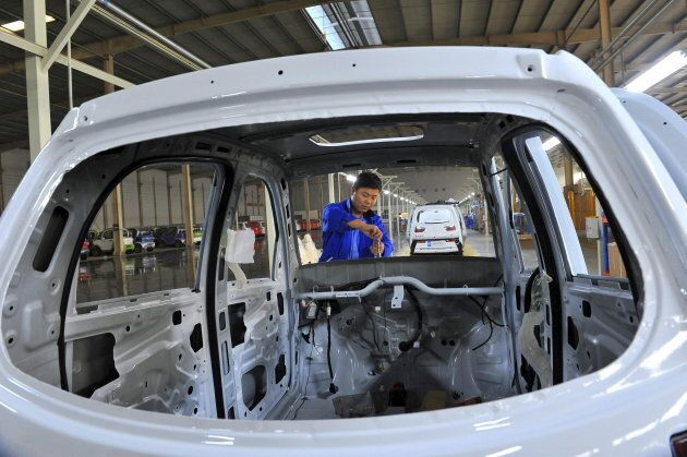 An employee assembles an electric car along a production line at a factory in Qingzhou, Shandong province, China.