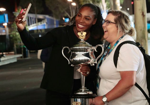Tennis - Australian Open - Melbourne Park, Melbourne, Australia - early 29/1/17 Serena Williams of the U.S. holds the Women's singles trophy as she poses with a fan Kate Salemme, after winning her final match.