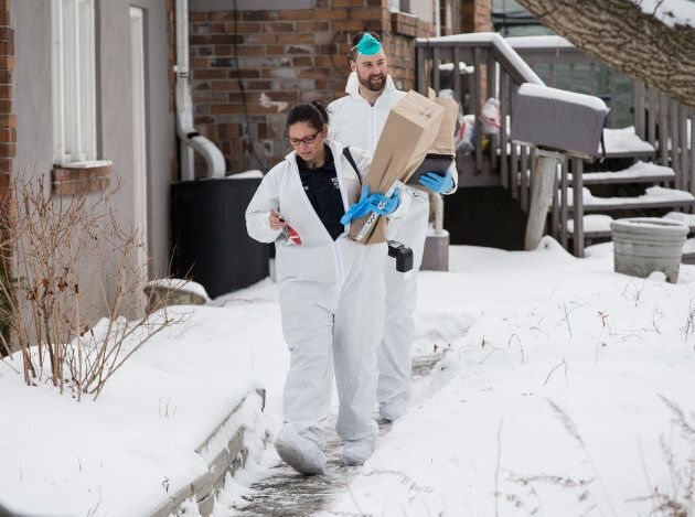 Forensic investigators remove evidence from inside the home at 53 Mallory Cresc.,