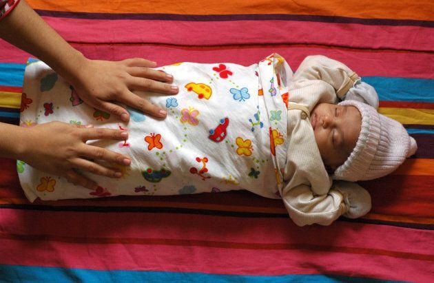 Woman adjusting baby's chador while he is asleep.