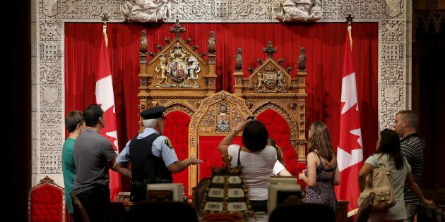 A guard talks to people touring the Senate chamber on Parliament Hill in Ottawa on July 24,
