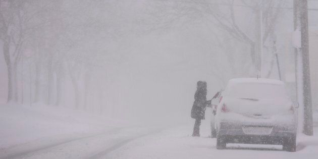 A woman cleans snow off her car as a storm brings white-out conditions to Halifax on
