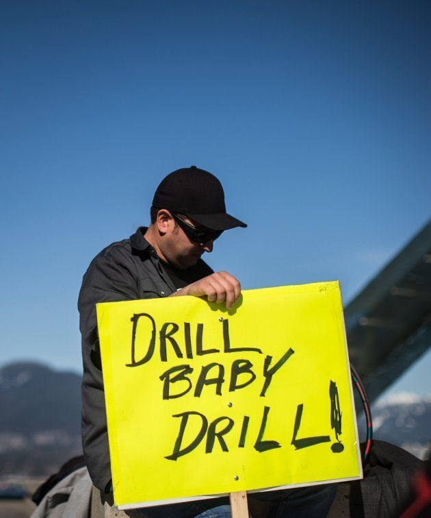 A man holds a sign while listening during a rally in support of the Kinder Morgan Trans Mountain pipeline...
