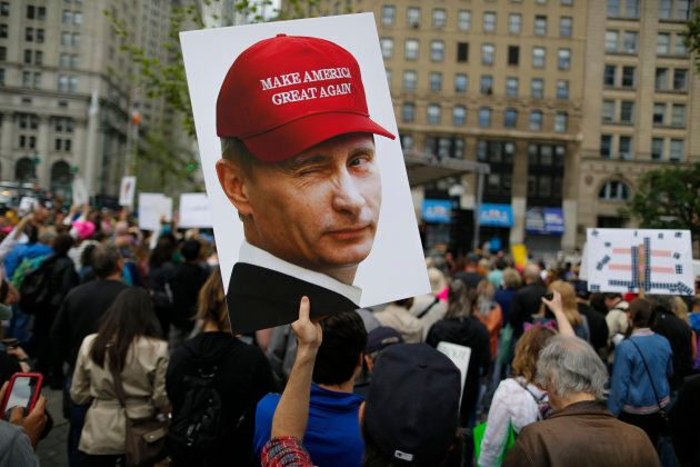 A demonstrator holds up a sign of Vladimir Putin during an