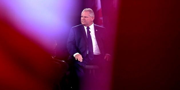 Before being elected Ontario PC Party leader, candidate Doug Ford is seen past Canadian flags as he participates...