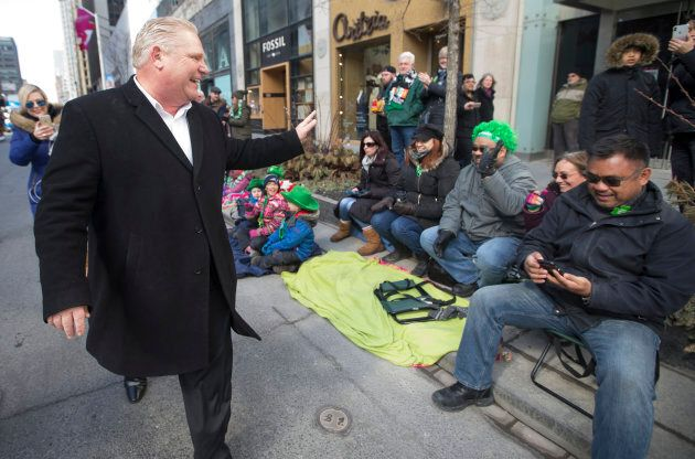 Newly minted Ontario PC Leader Doug Ford in the St. Patricks Day Parade waves to folks sitting on the...
