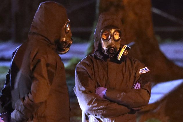 Police officers in forensics suits and protective masks work at the scene of the poisoning of Sergei...