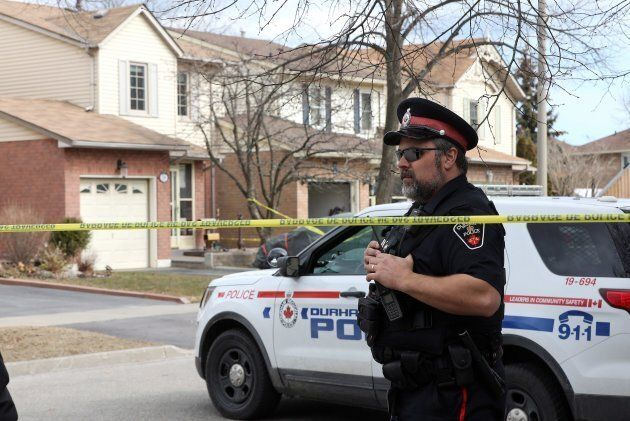 A police officer stands outside a home in Ajax, Ont., on