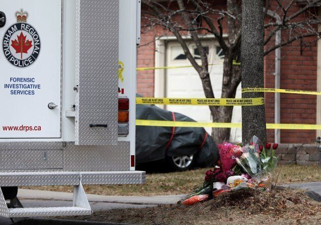 Flowers are seen next to a police forensics vehicle outside a home in Ajax, Ont., on