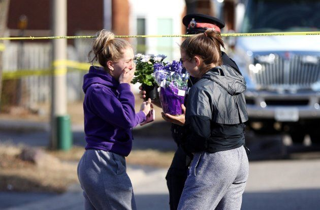 Mackenzie Cooper, 14, left and Cailynn Denoon hand over flowers to a police officer in a show of sympathy...