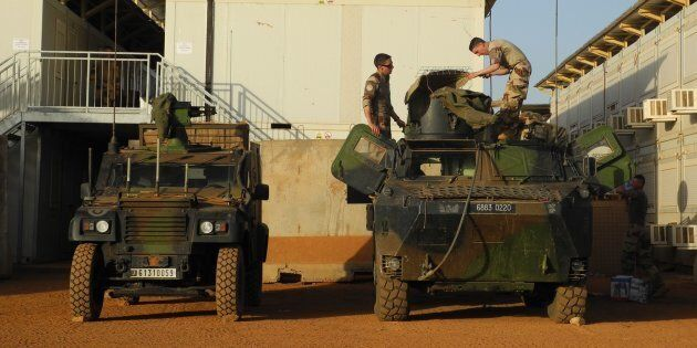 Soldiers of France's Barkhane mission stand next military vehicles on the military base in Gao, Mali...