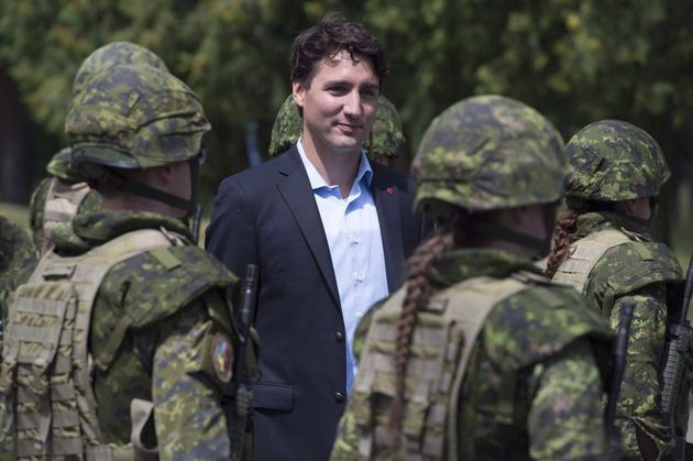 Prime Minister Justin Trudeau reviews an honour guard as they arrive at the International Peacekeeping...