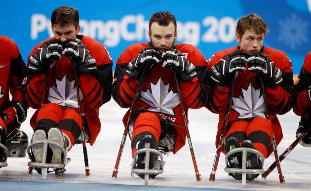 Canada players react during the victory ceremony after the gold medal hockey game on March 18,