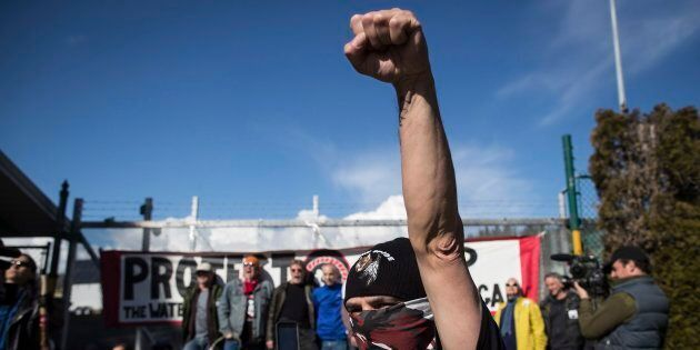 A protester raises his fist as others block a gate outside Kinder Morgan in Burnaby, B.C. on March 17,...