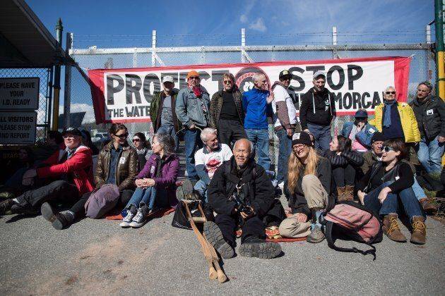 Protesters block a gate outside Kinder Morgan before RCMP officers moved in and arrested them for defying...