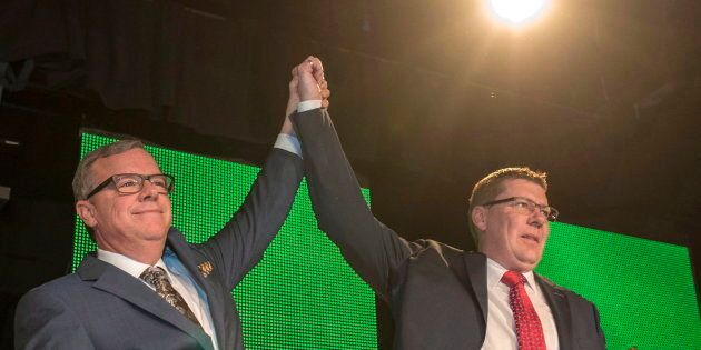 Former Saskatchewan premier Brad Wall, left, lifts the arm of Scott Moe, who won the party leadership...