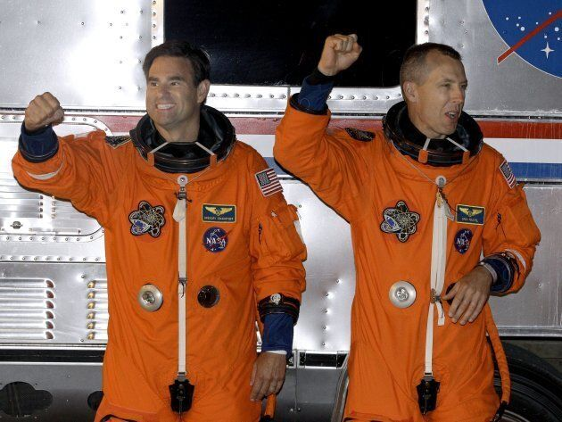 Mission specialist Greg Chamitoff, left, and mission specialist Drew Feustel pump their fists for photographers...