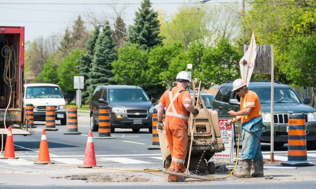 Two workers do repair work on a Toronto roadway.