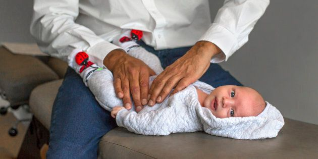 A chiropractor adjusts a one-month-old baby.