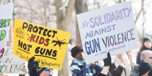 People hold up signs during a 'March for Our Lives' rally to show solidarity with the U.S. gun control...