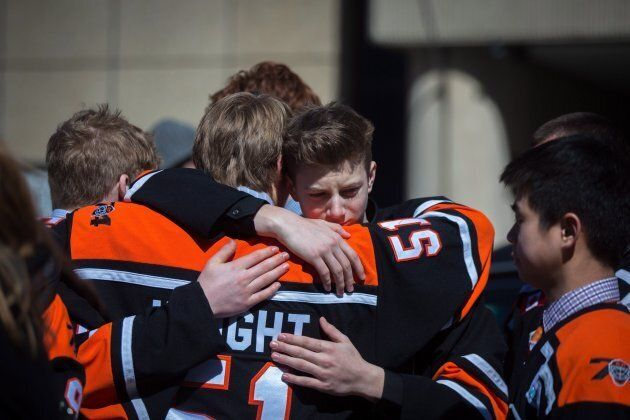 Teammates of Roy Pejcinovski hug outside the funeral for triple homicide victims Krassimira, Roy, and...