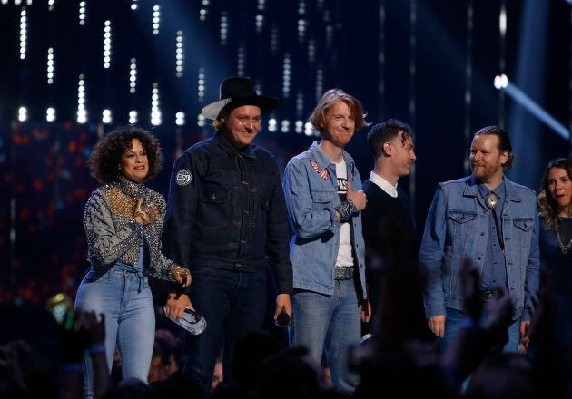 Win Butler (2nd from L) of Arcade Fire accepts the award for album of the year with the rest of the group...