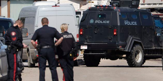 Calgary police officers stand at the scene of a shooting on March 27,