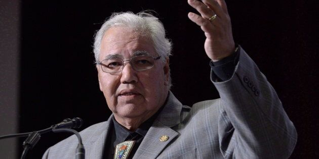 Commission chairman Justice Murray Sinclair raises his arm asking residential school survivors to stand...