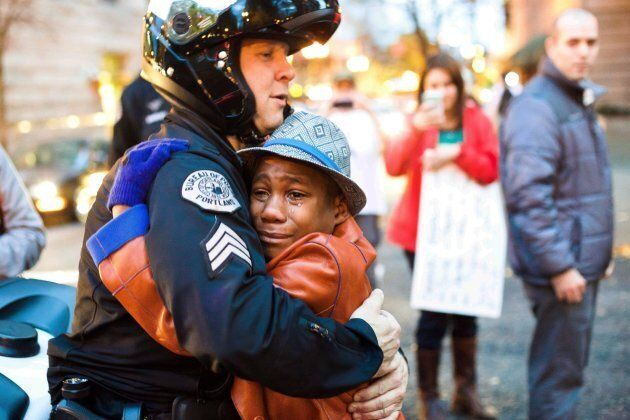 Portland police Sgt. Bret Barnum, left, and Devonte Hart, then 12, hug at a rally in Portland, Ore.,...