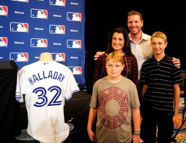 Roy Halladay is joined with his wife Brandy, sons Braden, right, and Ryan, center, before he announces...