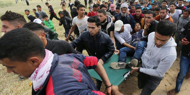 A wounded Palestinian is evacuated during clashes with Israeli troops, during a tent city protest along the Israel border with Gaza, demanding the right to return to their homeland, the southern Gaza Strip on March 30, 2018.