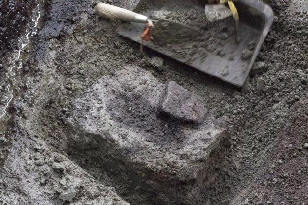 Dozens of ancient footprints, one of which is shown at the dig site on a British Columbia island, have...