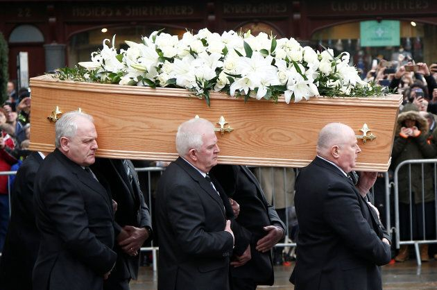 Pallbearers carry the coffin out of Great St. Mary's Church at the end of the funeral of theoretical...