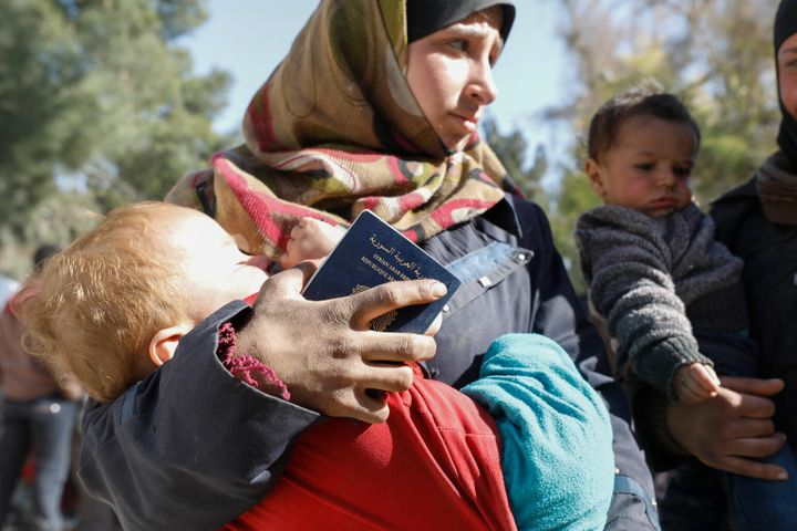 On 20 March 2018 in Adra in eastern Ghouta in the Syrian Arab Republic, a woman carries a child at the electricity complex in Adra, now home to around 13,000 people who have fled besieged eastern Ghouta.