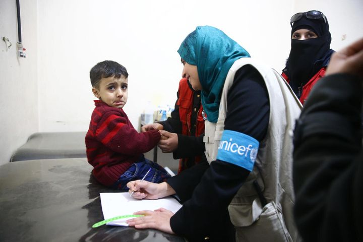 On 15 March 2018, UNICEF nutrition specialist, Rajia Sherhan, screens the nutrition status of a child at a health facility in Douma, eastern Ghouta.