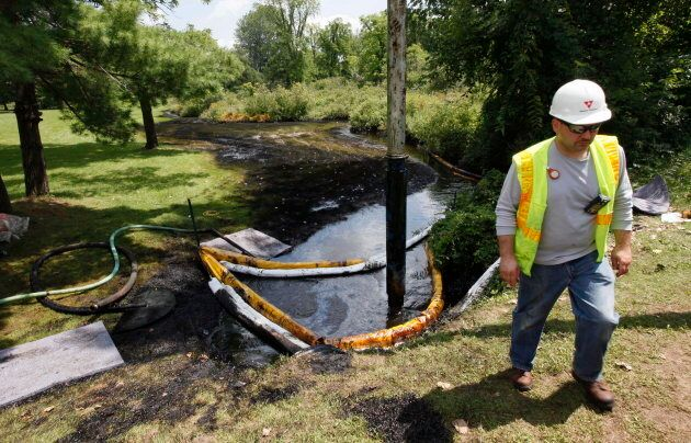 In this July 29, 2010 photo, a worker monitors the water in Talmadge Creek in Marshall Township, Mich., near the Kalamazoo River as oil from a ruptured pipeline is vacuumed out the water.