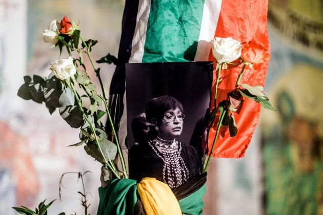 A black and white photograph of the late Winnie Madikizela-Mandela is surrounded by South African and African National Congress flags on a pole at the Old Durban Prison's Human Rights wall as South Africans gather to pay respect to the late activist during a candle vigil in Durban on April 2, 2018.